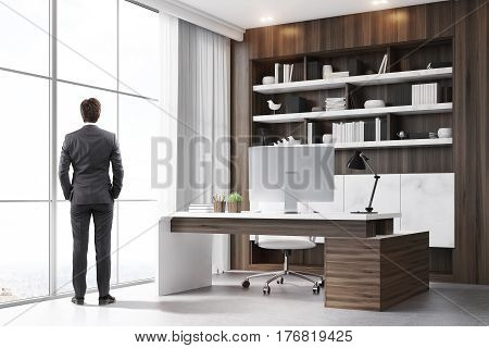 Rear view of a company CEO standing in his dark wood office with a bookcase a massive table and a computer. 3d renedirng.