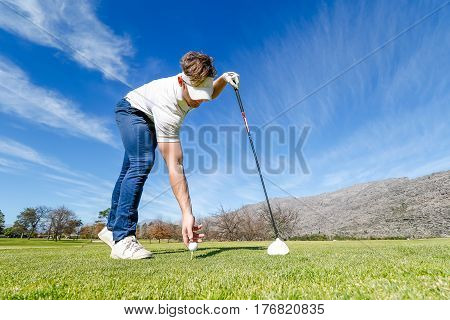 Wide Angle View Of A Golfer Teeing Off From A Golf Tee On A Bright Sunny Day On A Golf Course In Sou