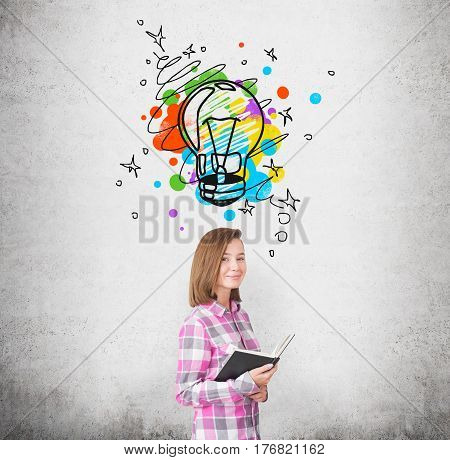 Portrait of a young woman wearing a pink checkered shirt and standing near a concrete wall with a colorful light bulb drawn above her head.