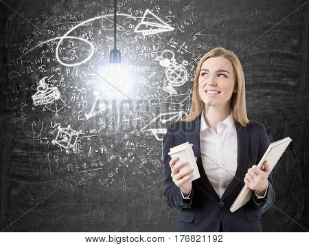 Portrait of a smiling businesswoman standing with her paper cup of coffee and a clipboard near a business idea sketch on a blackboard.
