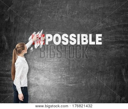 Rear view of a blond businesswoman covering the im part of the word impossible on a blackboard. Mock up