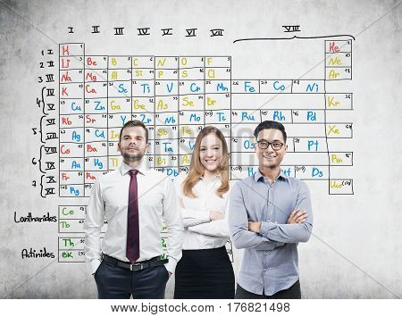 Portrait of a woman and her two male colleagues standing near a concrete wall with a periodic table drawn on it.