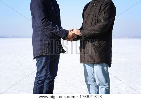 Happy gay couple holding hands together, outdoors