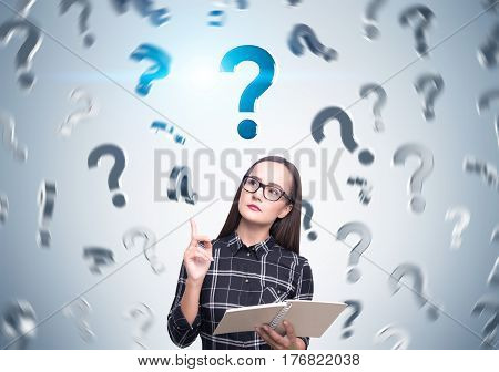 Portrait of a nerdy girl wearing glasses and standing in a checkered shirt with question marks falling around her.