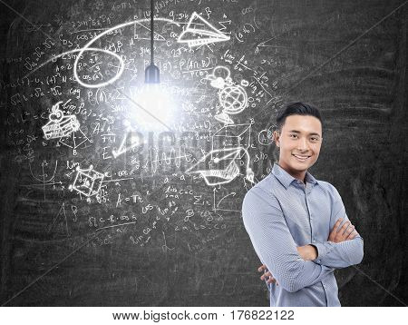 Portrait of a smiling Asian businessman wearing a blue shirt and standing with crosed arms near a blackboard with a business idea sketch.