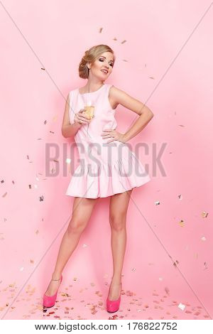 Pretty young woman with a sham glass posing on the pink background. Vertical studio shot.
