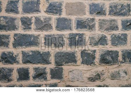 Texture of black basalt brick wall inside the house