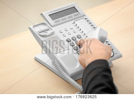 Hand of man dialing telephone number in office