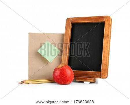 Blackboard, paper lunch bag with reminder and apple on white background