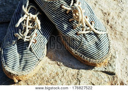 picture of vintage old shabby sneakers at seacost, real forgotten shoes close up