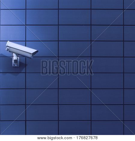 Horizontal front view of a surveillance monitoring white camera viewed from a side with blue background wall of metallic plates copyspace on the right