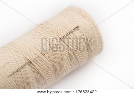 close up of metal sewing needle eye and spool on light colored thread on white background