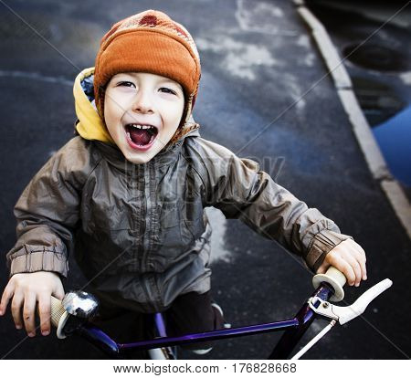 little cute real boy on bicycle smiling close up emotional posing autumn street, lifestyle real people concept