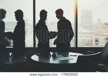 Silhouette of young serious bearded businessman and his colleague during meeting looking quarterly report on screen of wireless digital tablet in dark office room near window with cityscape outside