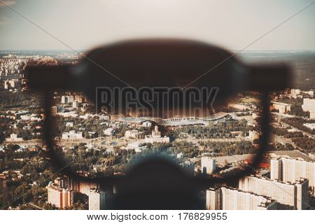 Blurred silhouette of binocular in foreground and summer cityscape in background from very high point view of Moscow city and VDNKh district on sunny day with many residential buildings and parks
