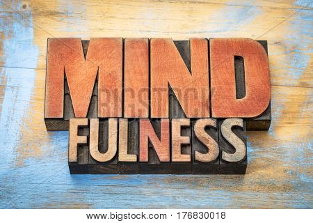 mindfulness word abstract  or banner - awareness concept - text in vintage letterpress wood type stained by color inks against grunge wooden background
