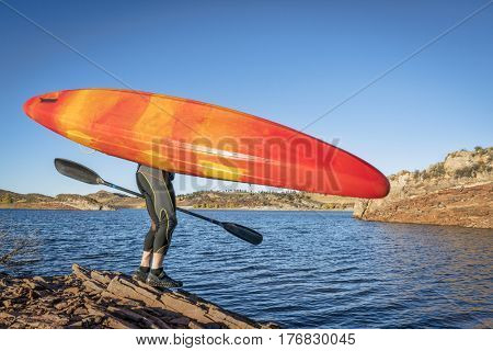 portaging and launching kayak on lake shore, Horsetooth REservoir, Colorado