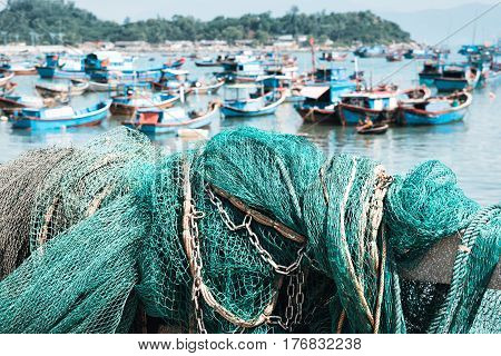 Fishing net in the harbor. Green fishing net.Sea and Boats on background
