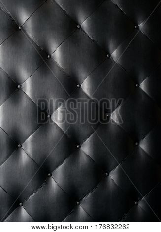 Black leather button tufted texture background  close-up