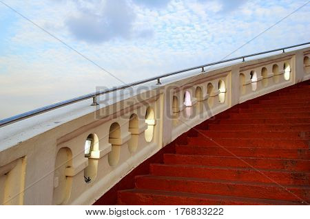 Travel to Bangkok Thailand. The red stairs with the white railing on the background of the blue sky.