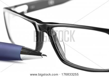 Close up shot of spectacles and blue pen