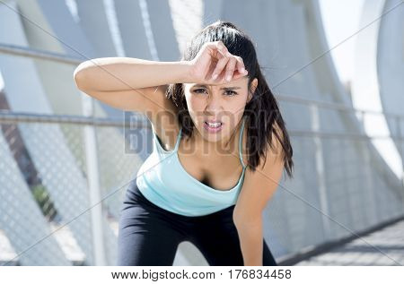 young beautiful and athletic sport woman tired and exhausted breathing and cooling down after running in urban training workout on modern metal city bridge in female runner body care concept