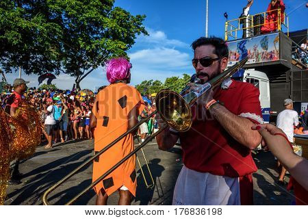 RIO DE JANEIRO, BRAZIL - FEBRUARY 28, 2017: Musician playing trombones on the background of platform of Bloco Orquestra Voadora in Flamengo Park, Carnaval 2017