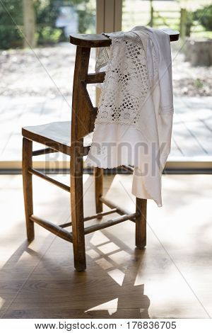 White Embroidered Cloth Hanging On A Wooden Chair Backrest