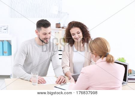 Young couple signing contract at insurance agency office poster