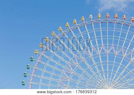 Ferris wheel against blue sky background in amusement park Japan