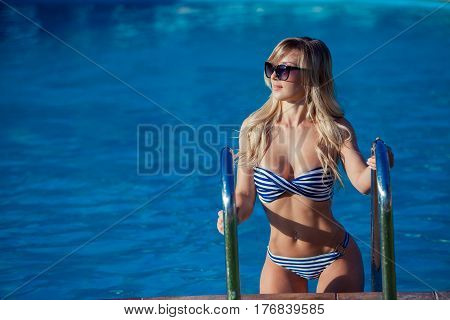 Beautiful young woman in a pretty swimsuit is standing on a stairs in the swimming pool. She is smiling so wonderful