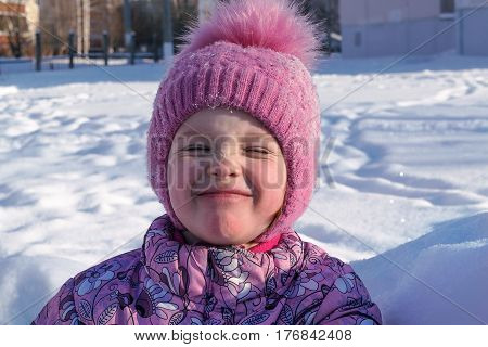 The girl in the Park in winter closed his eyes. White lies the snow. The little girl is wearing a jacket and hat pink. The girl is smiling and is in a playful mood. Cheerful and happy. Hat with bubo.