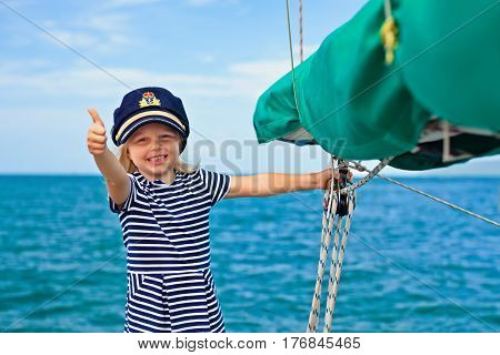 Happy little baby captain on board of sailing yacht watching offshore sea on summer cruise. Travel adventure yachting with child on family vacation. Kid clothing in sailor style nautical fashion.