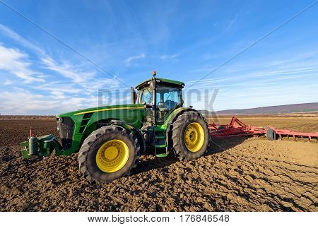 Varna Bulgaria - March 5 2017 Ploughing a field with John Deere tractor. John Deere was manufactured in 1995-1999 and it has JD 7.6L or 8.1L 6-cyl diesel engine.