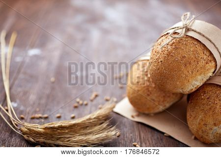 Bread loaf rustic selection of rye, soda, bloomer breads, with granary and oated rolls and ears of wheat. Natural products. Delicious food. Bread and baked goods on the brown background. Bakery and pastry.