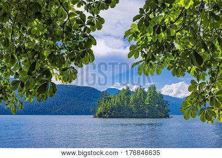 View of an Island framed by trees on Harrison Lake near Harrison Hot Springs British Columbia Canada