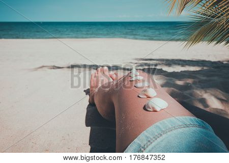 Relaxation and Leisure in summer - Seashell on tanned girl leg at tropical beach in summer. vintage color tone