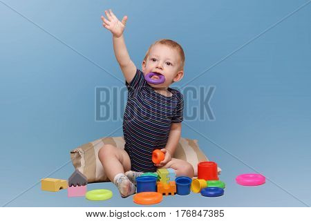 Funny kid playing toys. Child playing with colorful toys over blue background. Adorable baby boy. Baby teething.