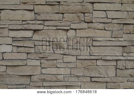Brick wall of uneven stone of different sizes for texture and background.
