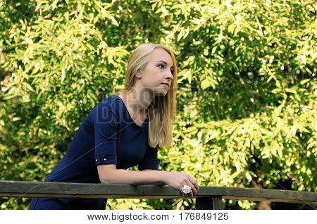 Blonde girl is leaning on wooden railing