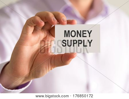 Businessman Holding A Card With Money Supply Message