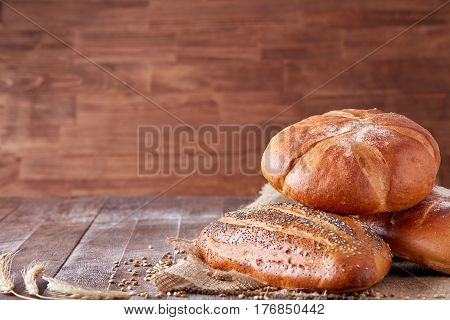 Warm baked bread, tasty crunchy buns, healthy food on dinner table, with text space. Brown wooden background. Cloth linen, wheat. Food, baker, tasty.