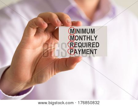 Businessman Holding A Card With Mmrp Minimum Monthly Required Payment Message
