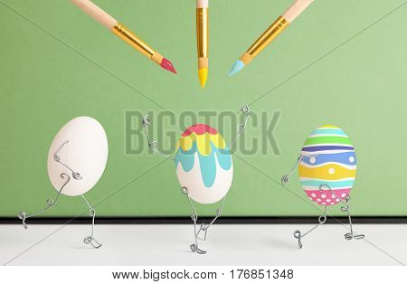 Paintbrushes is painting Easter decor on eggs on green background. Eggs have legs and arms.