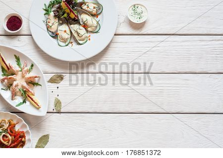 White wooden table with seafood meals free space. Top view on assortment of gourmet food, free space for text. Mediterranean cuisine, luxury lifestyle, restaurant menu concept