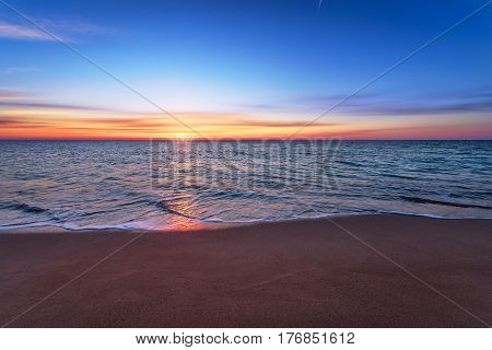 Brilliant ocean beach sunrise. Blue sky and  golden snads