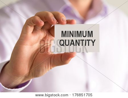Businessman Holding A Card With Minimum Quantity Message