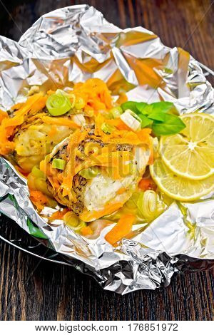 Pike With Leeks And Carrots In Foil On Dark Board
