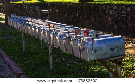 Row Of Metal Mailboxes With Flags Up At Sunset