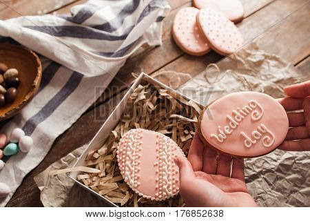 Packing sweets into gift box free space. Top view on female hands with two cookies with pink glaze and wedding day words on it. Preparing dessert for celebration party concept